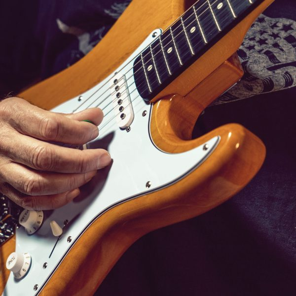 closeup of hand playing DSCO3913 electric guitar